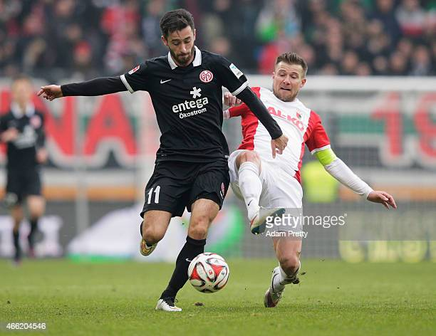 Daniel Baier of FC Augsburg tackles Yunus Malli of FSV Mainz 05 during the Bundesliga match betwen FC Augsburg and FSV Mainz 05 at SGL Arena on March...
