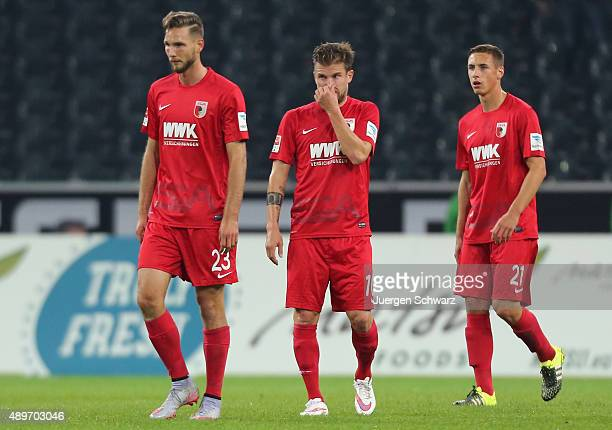 Daniel Baier touches his nose between Tim Matavz and Dominik Kohr during the Bundesliga match between Borussia Moenchengladbach and FC Augsburg at...