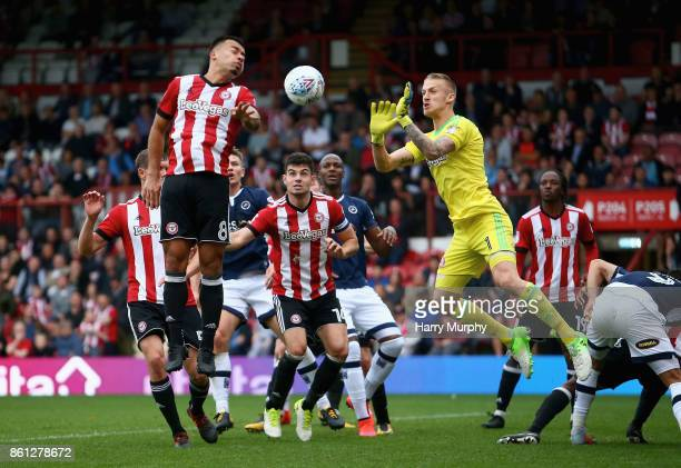 Daniel Bentley and Nico Yennaris of Brentford attmept to clear a corner during the Sky Bet Championship match between Brentford and Millwall at...