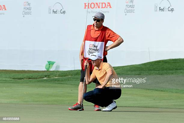 Daniel Berger and his caddie line up a putt on the 18th green during the continuation of the fourth round of The Honda Classic at PGA National Resort...
