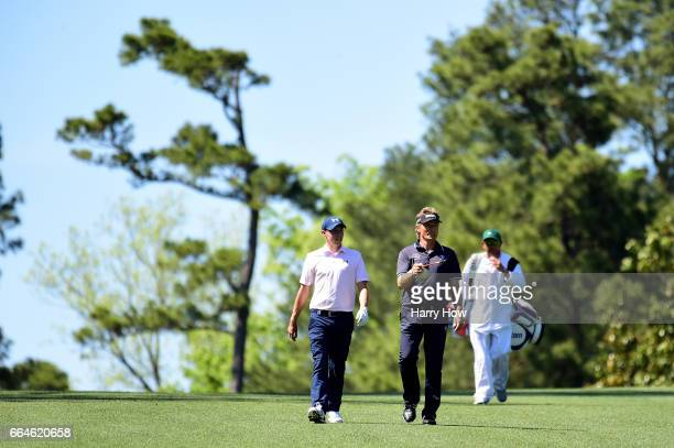 Daniel Berger of the United States and Bernhard Langer of Germany walk during a practice round prior to the start of the 2017 Masters Tournament at...