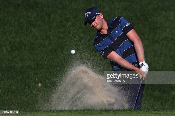 Daniel Berger of the United States plays a shot from a bunker on the 18th green during the final round of the Travelers Championship at TPC River...