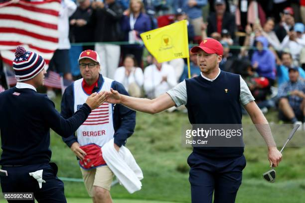 Daniel Berger of the US Team celebrates with Brooks Koepka reacts on the 11th green as Berger and Justin Thomas go one up over Jhonattan Vegas of...