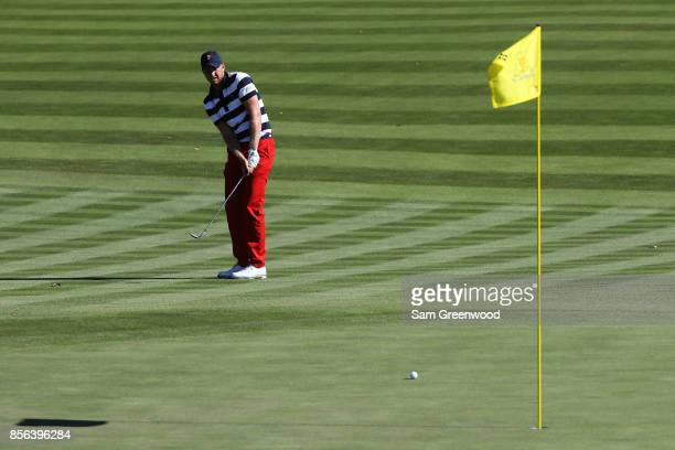 Daniel Berger of the US Team chips in on the 11th green during Sunday singles matches of the Presidents Cup at Liberty National Golf Club on October...