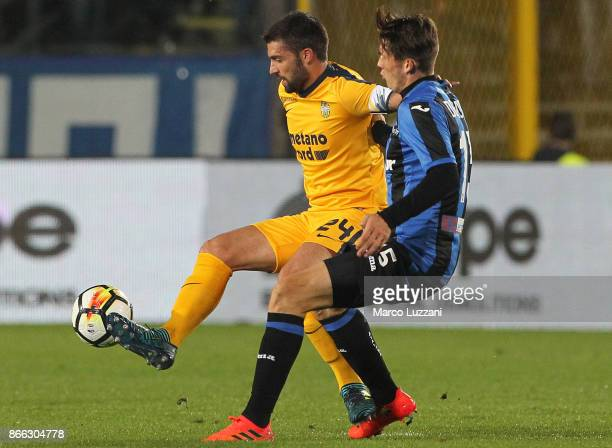 Daniel Bessa of Hellas Verona FC is challenged by Marten De Roon of Atalanta BC during the Serie A match between Atalanta BC and Hellas Verona FC at...