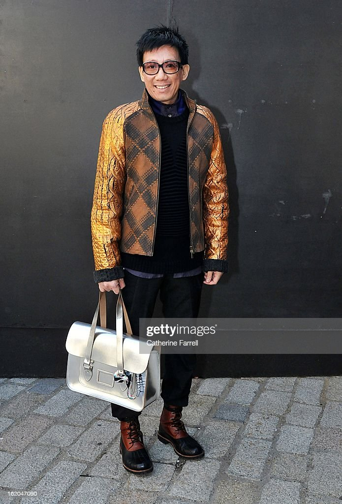 Daniel Boey, Fashion Director from Singapore wearing British labels and over here with a team of fashion buyers from Singapore wearing Body bound mettalic bronze sprayed jacket, Navy sweather by Body Bound, tee shirt Silver Bay, trousers Comme de Garcons, and silver mettalic satchel a collaboration between Van Assche and Cambridge satchels, sunglasses by Thakoon Thai NY based label, Boots by Diamond Walker a bespoke Korean shoe company at London Fashion Week Fall/Winter 2013/14 on February 18, 2013 in London, England.