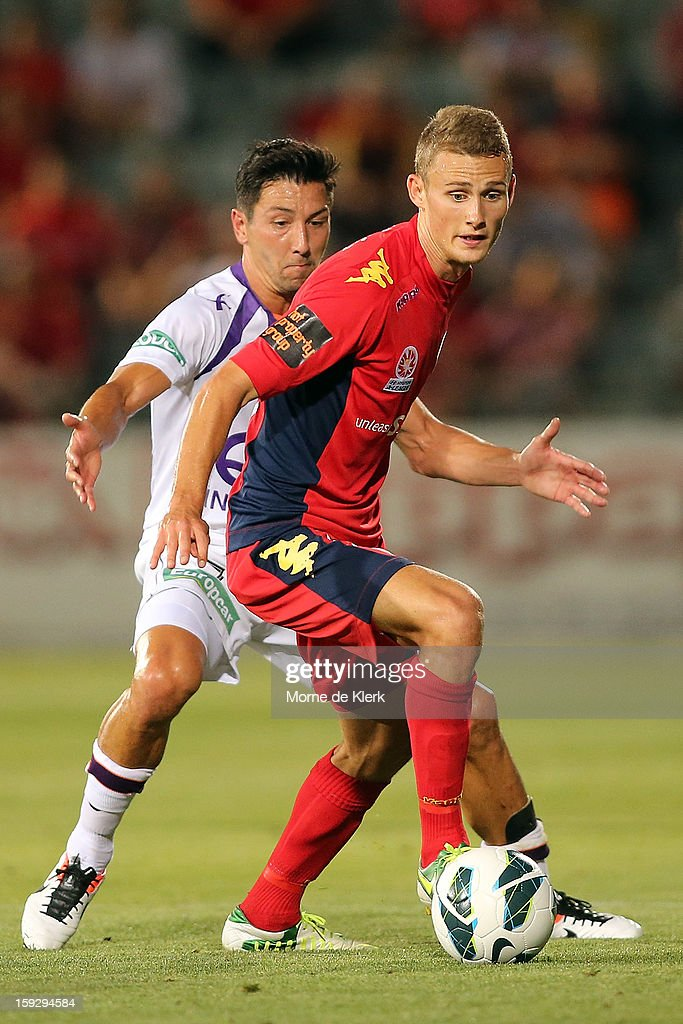 Daniel Bowles of Adelaide gets away from Jacob Burns of Perth during the round 16 A-League match between Adelaide United and the Perth Glory at Hindmarsh Stadium on January 11, 2013 in Adelaide, Australia.