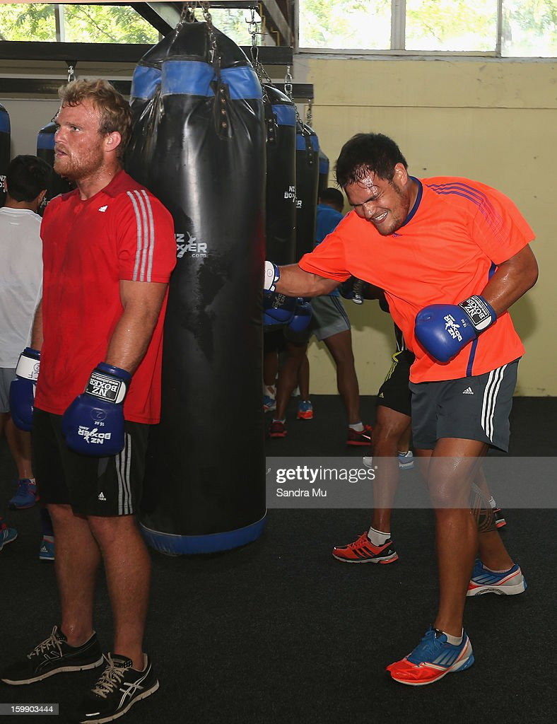 Daniel Braid (L) holds the bag for Angus Ta'avao during a Blues training session with Shane Cameron at Shane Cameron Fitness on January 23, 2013 in Auckland, New Zealand.
