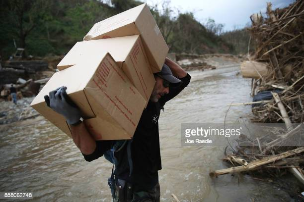 Daniel Braithwaite carries boxes of MRE's as he helps US Army 1st Special Forces Command soldiers as they deliver food and water in the wake of the...