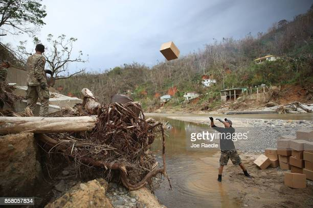 Daniel Braithwaite prepares to catch a box of MRE's as helps US Army 1st Special Forces Command soldiers as they deliver food and water to people...