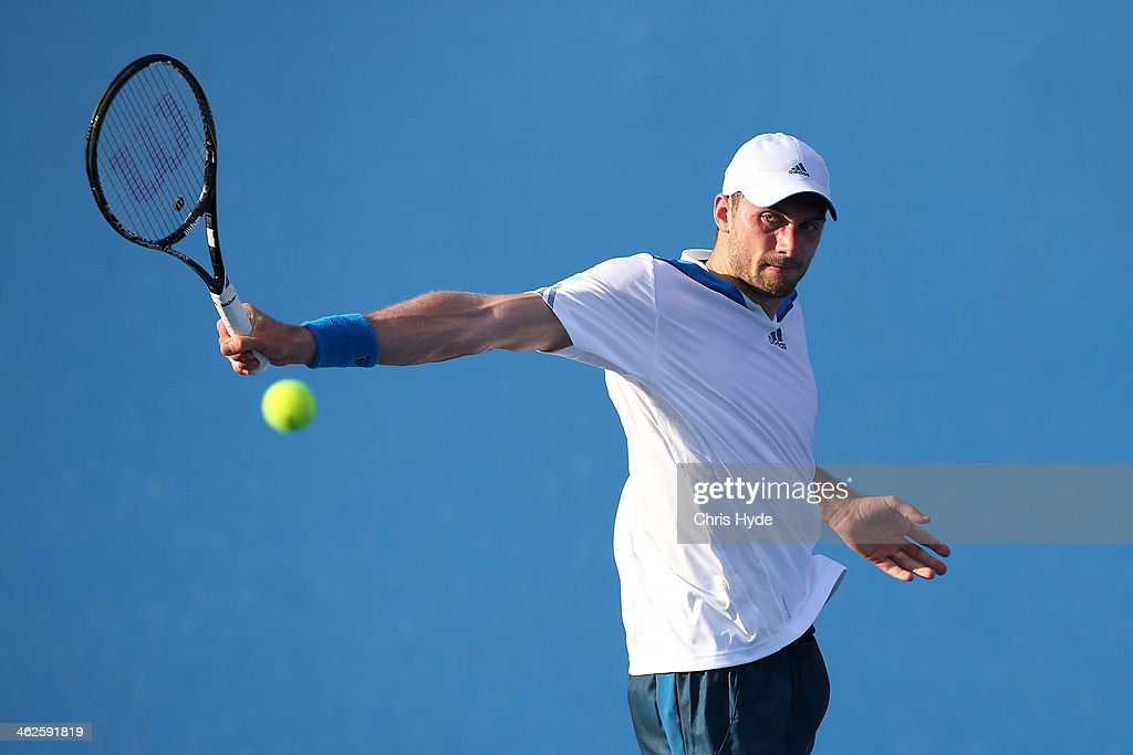 Daniel Brands of Germany plays a backhand in his first round match against Gilles Simon of France during day two of the 2014 Australian Open at...