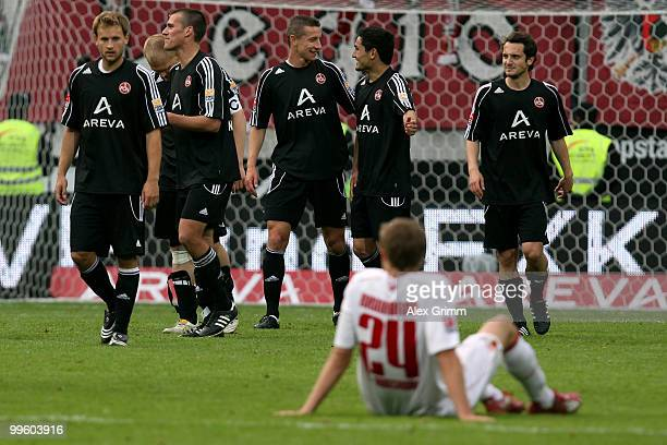 Daniel Brinkmann of Augsburg sits on the pitch as players of Nuernberg celebrate after the Bundesliga play off leg two match between FC Augsburg and...