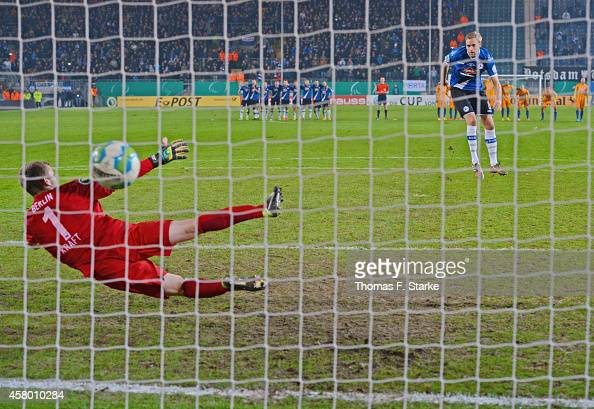 Daniel Brinkmann of Bielefeld scores a penalty against Thomas Kraft of Berliner during the DFB Cup match between Arminia Bielefeld and Hertha BSC at...