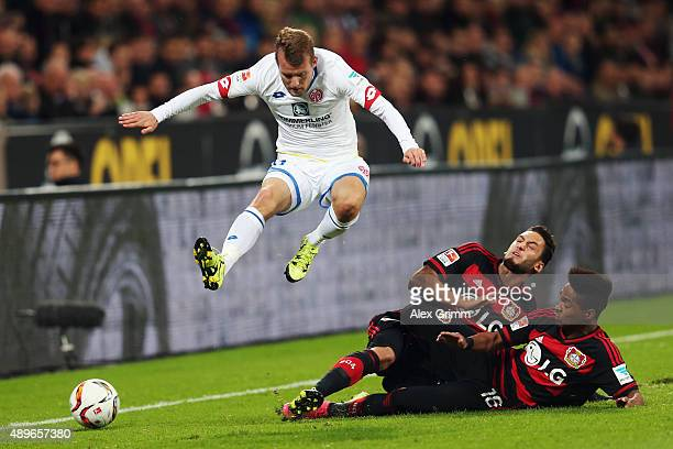 Daniel Brosinski of Mainz is challenged by Hakan Calhanoglu and Wendell of Leverkusen during the Bundesliga match between Bayer Leverkusen and 1 FSV...