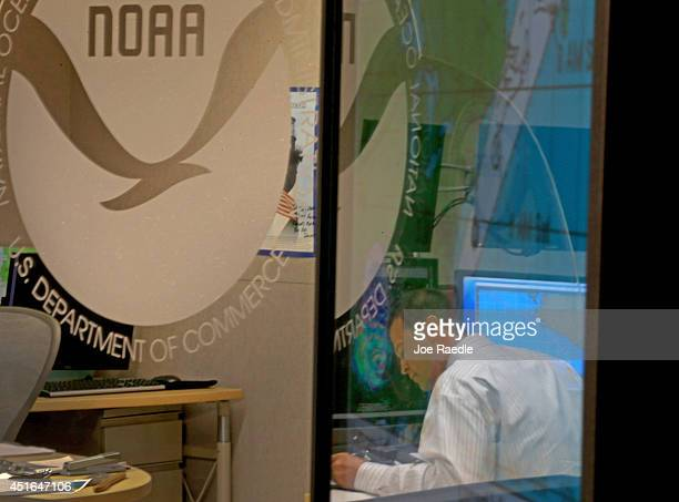 Daniel Brown Senior Hurricane Specialist at the National Hurricane Center is seen reflected in a television screen as he tracks Hurricane Arthur the...