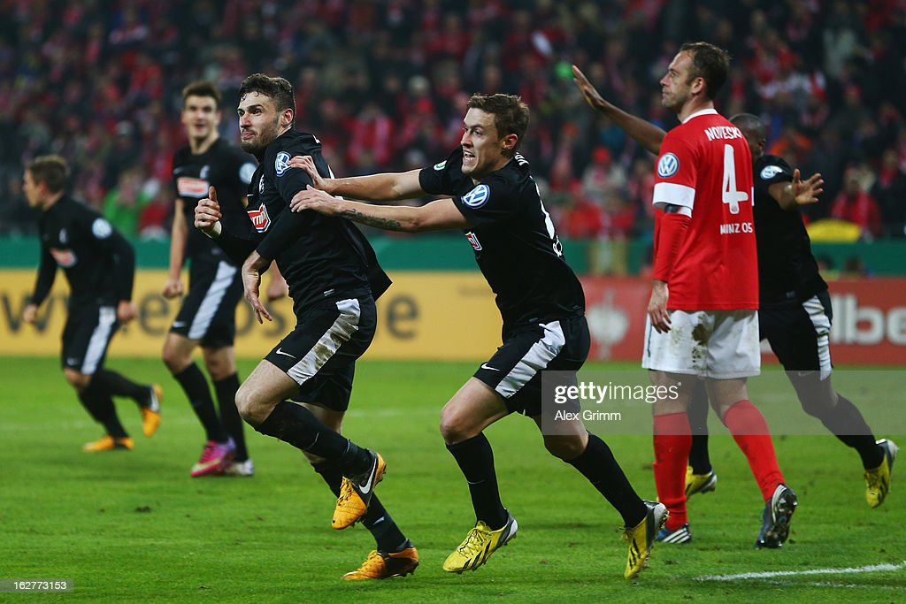 Daniel Caligiuri of Freiburg celebrates his team's third goal with team mate <a gi-track='captionPersonalityLinkClicked' href=/galleries/search?phrase=Max+Kruse&family=editorial&specificpeople=3945507 ng-click='$event.stopPropagation()'>Max Kruse</a> as <a gi-track='captionPersonalityLinkClicked' href=/galleries/search?phrase=Nikolce+Noveski&family=editorial&specificpeople=649271 ng-click='$event.stopPropagation()'>Nikolce Noveski</a> of Mainz reacts during the DFB Cup Quarter Final match between FSV Mainz 05 and SC Freiburg at Coface Arena on February 26, 2013 in Mainz, Germany.