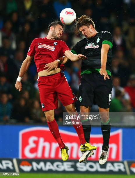 Daniel Caligiuri of Freiburg jumps for a header with Sebastian Proedl of Bremen during the Bundesliga match between SC Freiburg and SV Werder Bremen...