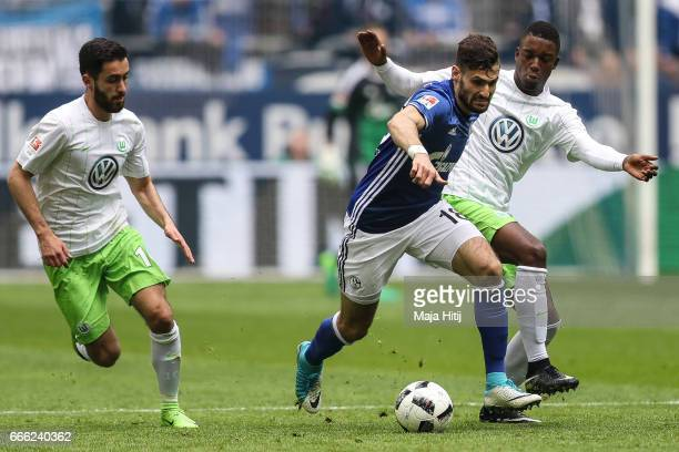 Daniel Caligiuri of Schalke and Richedly Bazoer of Wolfsburg battle for the ball during the Bundesliga match between FC Schalke 04 and VfL Wolfsburg...