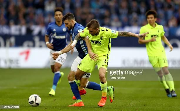 Daniel Caligiuri of Schalke battles for the ball with Konstantinos Stafylidis of Augsburg during the Bundesliga match between FC Schalke 04 and FC...