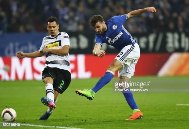 Daniel Caligiuri of Schalke shoots past Timothee Kolodziejczak of Borussia Moenchengladbach during the UEFA Europa League Round of 16 first leg match...