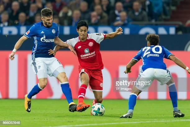 Daniel Caligiuri of Schalke Yoshinori Muto of Mainz and Thilo Kehrer of Schalke battle for the ball during the Bundesliga match between FC Schalke 04...
