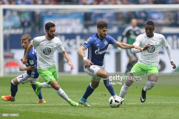Daniel Caligiuri of Schalke Yunus Malli of Wolfsburg and Richedly Bazoer of Wolfsburg battle for the ball during the Bundesliga match between FC...