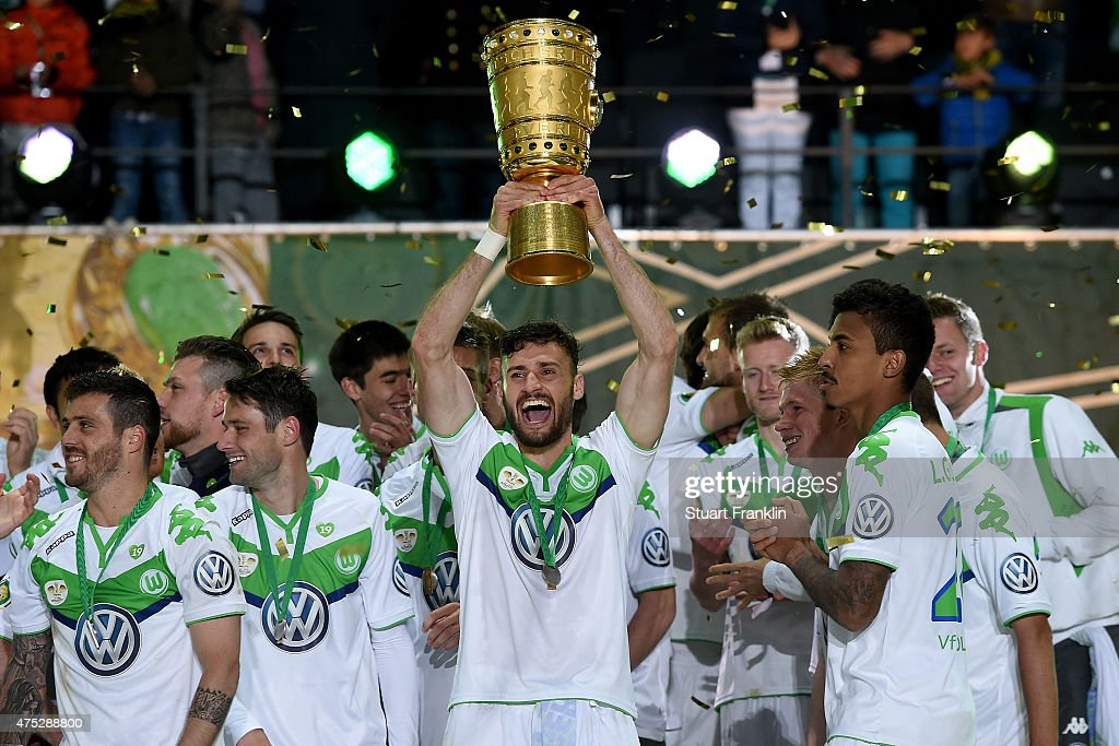 <a gi-track='captionPersonalityLinkClicked' href=/galleries/search?phrase=Daniel+Caligiuri&family=editorial&specificpeople=6495349 ng-click='$event.stopPropagation()'>Daniel Caligiuri</a> of VfL Wolfsburg lifts the trophy with team mates to celebrate victory after the DFB Cup Final match between Borussia Dortmund and VfL Wolfsburg at Olympiastadion on May 30, 2015 in Berlin, Germany