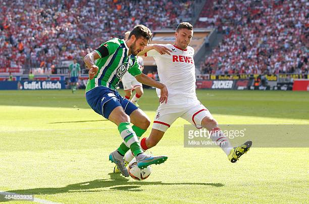 Daniel Caligiuri of Wolfsburg challenges Jonas Hector of Cologne during the Bundesliga match between 1 FC Koeln and VfL Wolfsburg at...