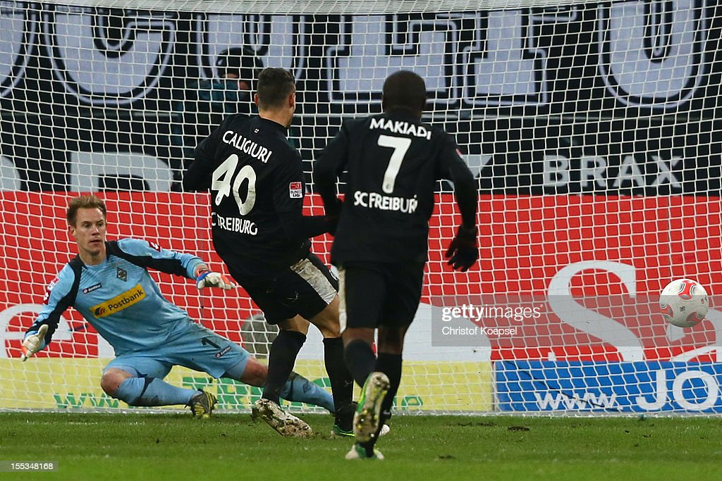 Daniel Caliguri of Freiburg (C) scores his first goal by penalty against <a gi-track='captionPersonalityLinkClicked' href=/galleries/search?phrase=Marc-Andre+ter+Stegen&family=editorial&specificpeople=5528638 ng-click='$event.stopPropagation()'>Marc-Andre ter Stegen</a> of Moenchengladbach (L) during the Bundesliga match between VfL Borussia Moenchengladbach and SC Freiburg at Borussia Park Stadium on November, 2012 in Moenchengladbach, Germany.