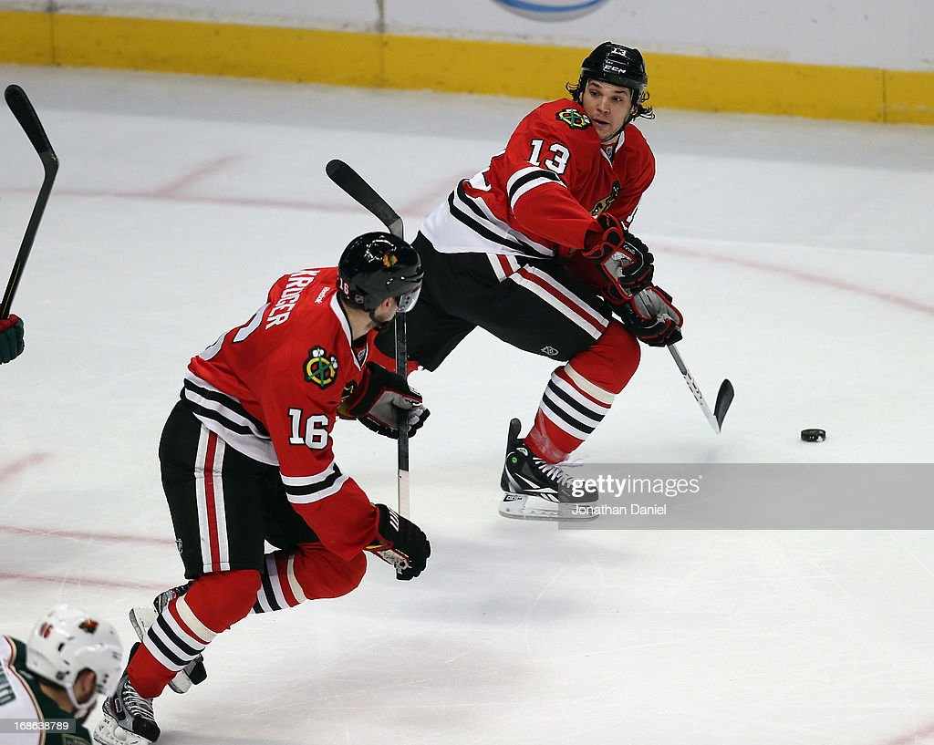 <a gi-track='captionPersonalityLinkClicked' href=/galleries/search?phrase=Daniel+Carcillo&family=editorial&specificpeople=2116181 ng-click='$event.stopPropagation()'>Daniel Carcillo</a> #13 and Marcus Kruger #16 of the Chicago Blackhawks move the puck up the ice against the Minnesota Wild in Game Five of the Western Conference Quarterfinals during the 2013 NHL Stanley Cup Playoffs at the United Center on May 9, 2013 in Chicago, Illinois. The Blackhawks defeated the Wild 5-1 to win the series.