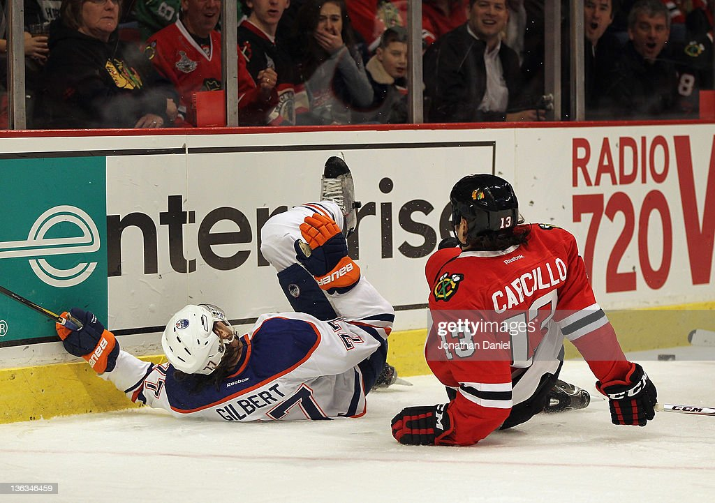 Daniel Carcillo of the Chicago Blackhawks and Tom Gilbert of the Edmonton Oilers fall to ice after Carcillo boarded Gilbert in the second period at...