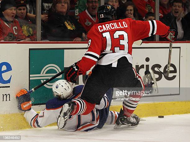 Daniel Carcillo of the Chicago Blackhawks boards Tom Gilbert of the Edmonton Oilers at the United Center on January 2 2012 in Chicago Illinois