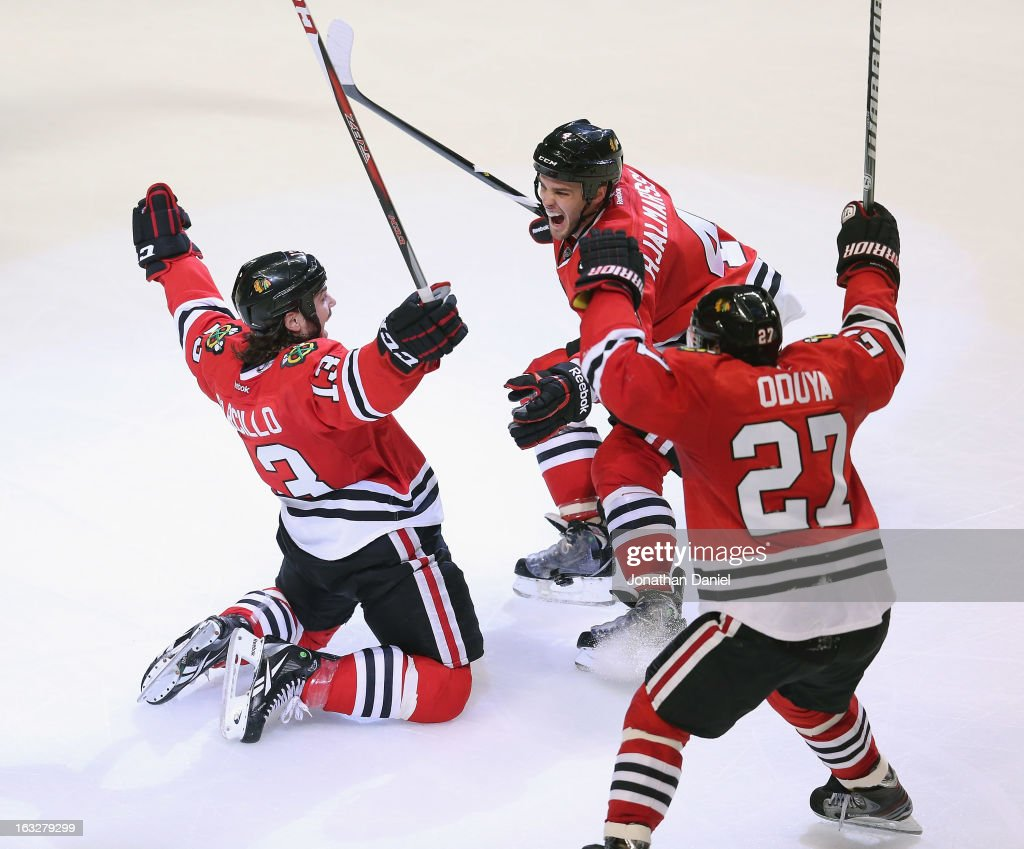 <a gi-track='captionPersonalityLinkClicked' href=/galleries/search?phrase=Daniel+Carcillo&family=editorial&specificpeople=2116181 ng-click='$event.stopPropagation()'>Daniel Carcillo</a> #13 of the Chicago Blackhawks celebrates his game-winning goal with teammates <a gi-track='captionPersonalityLinkClicked' href=/galleries/search?phrase=Niklas+Hjalmarsson&family=editorial&specificpeople=2006442 ng-click='$event.stopPropagation()'>Niklas Hjalmarsson</a> #4 and <a gi-track='captionPersonalityLinkClicked' href=/galleries/search?phrase=Johnny+Oduya&family=editorial&specificpeople=3944055 ng-click='$event.stopPropagation()'>Johnny Oduya</a> #27 against the Colorado Avalanche at the United Center on March 6, 2013 in Chicago, Illinois. The Blackhawks defeated the Avalanche 3-2.