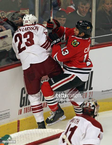 Daniel Carcillo of the Chicago Blackhawks checks Oliver EkmanLarsson of the Phoenix Coyotes at the United Center on December 5 2011 in Chicago...