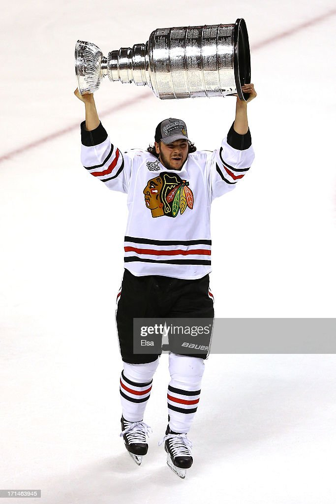 Daniel Carcillo #13 of the Chicago Blackhawks hoists the Stanley Cup Trophy after defeating the Boston Bruins in Game Six of the 2013 NHL Stanley Cup Final at TD Garden on June 24, 2013 in Boston, Massachusetts. The Chicago Blackhawks defeated the Boston Bruins 3-2.