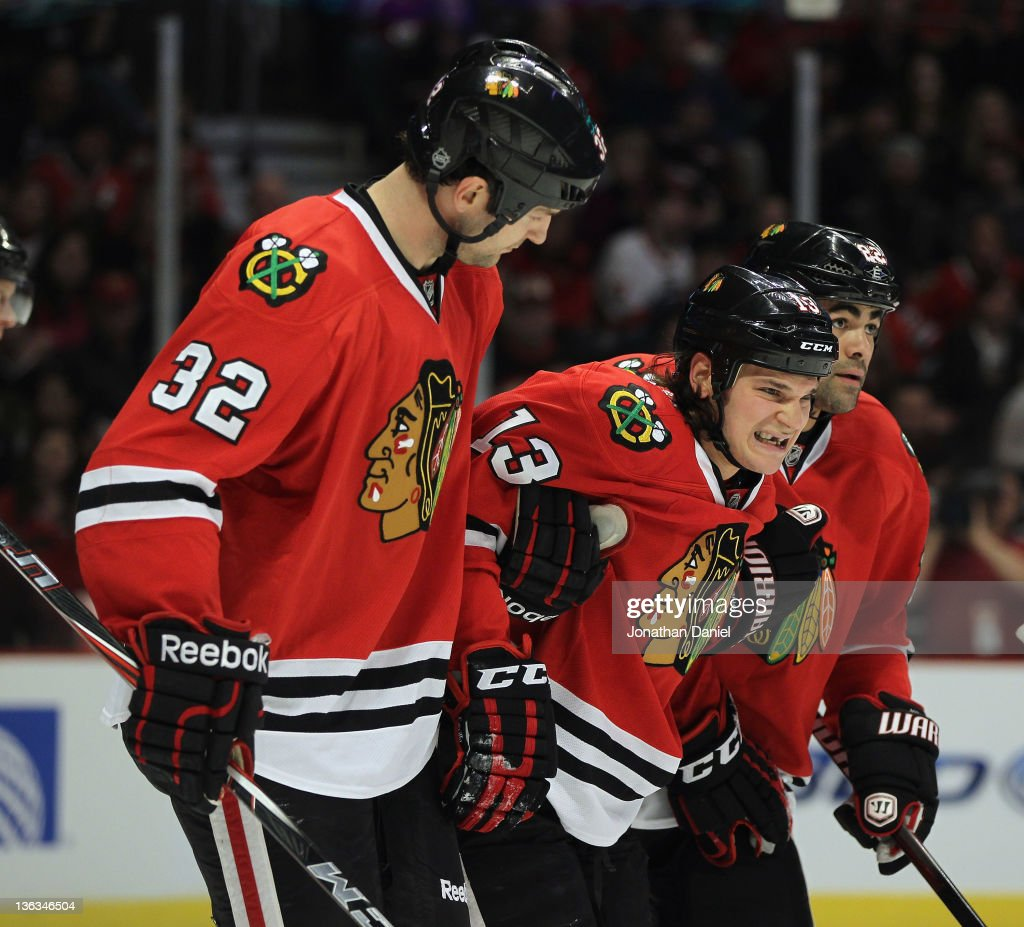 Daniel Carcillo of the Chicago Blackhawks is helped off of the ice by John Scott and Jamal Mayers after being injured while boarding Tom Gilbert of...