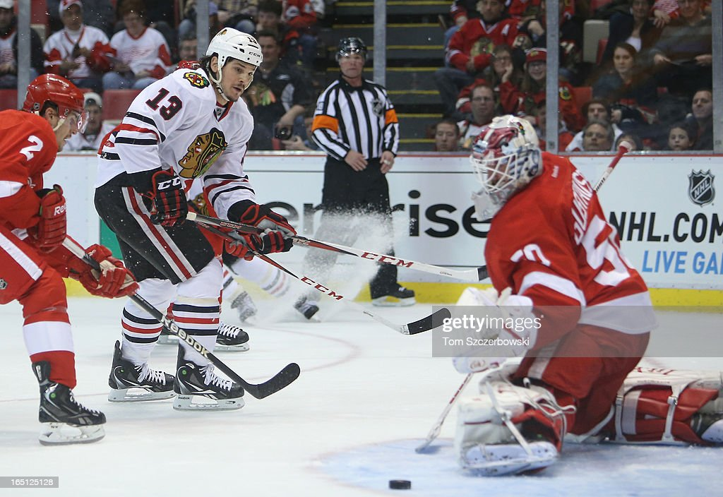 <a gi-track='captionPersonalityLinkClicked' href=/galleries/search?phrase=Daniel+Carcillo&family=editorial&specificpeople=2116181 ng-click='$event.stopPropagation()'>Daniel Carcillo</a> #13 of the Chicago Blackhawks shoots the puck during an NHL game as <a gi-track='captionPersonalityLinkClicked' href=/galleries/search?phrase=Jonas+Gustavsson&family=editorial&specificpeople=886789 ng-click='$event.stopPropagation()'>Jonas Gustavsson</a> #50 of the Detroit Red Wings makes a save at Joe Louis Arena on March 31, 2013 in Detroit, Michigan.