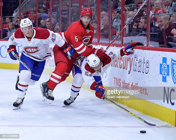 Daniel Carr and Charles Hudon of the Montreal Canadiens battle Noah Hanifin of the Carolina Hurricanes for possession behind the net during the game...