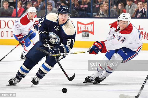 Daniel Carr of the Montreal Canadiens hits the stick of Ryan Murray of the Columbus Blue Jackets as he skates with the puck during the first period...