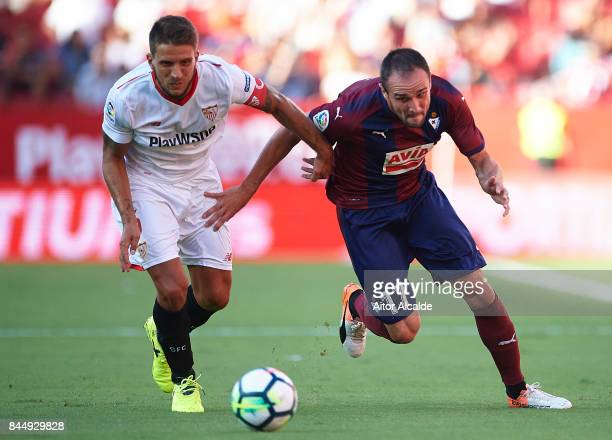 Daniel Carrico of Sevilla FC competes for the ball with Enrique Garcia of SD Eibar during the La Liga match between Sevilla and Eibar at Estadio...
