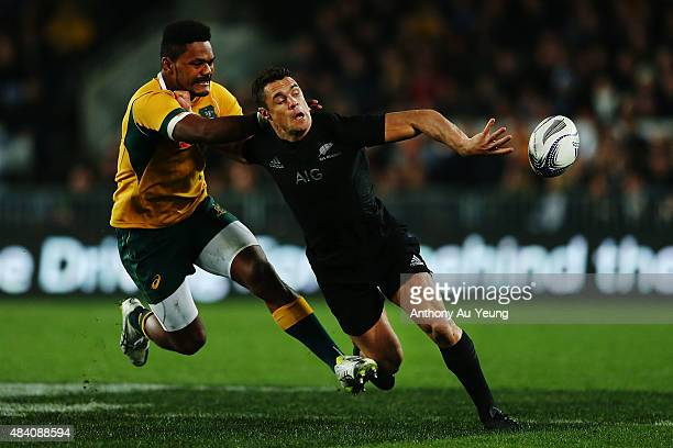 Daniel Carter of New Zealand offloads in the tackle from Henry Speight of Australia during The Rugby Championship Bledisloe Cup match between the New...