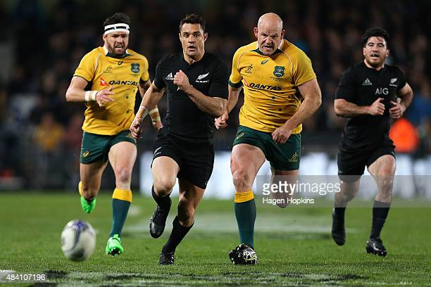 Daniel Carter of the All Blacks chases down a loose ball under pressure from Stephen Moore of the Wallabies during The Rugby Championship Bledisloe...