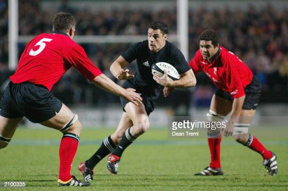 Daniel Carter of the All Blacks runs between Gareth Llewellyn and Colin Charvis during the test match between the New Zealand All Blacks and Wales at...