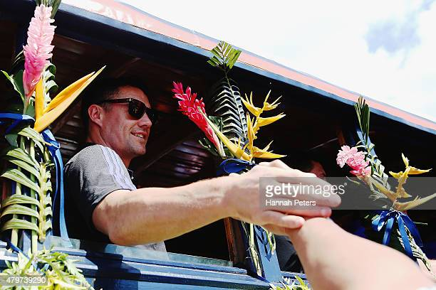 Daniel Carter of the New Zealand All Blacks waves to fans during a parade down the main street of Apia on July 7 2015 in Apia Samoa
