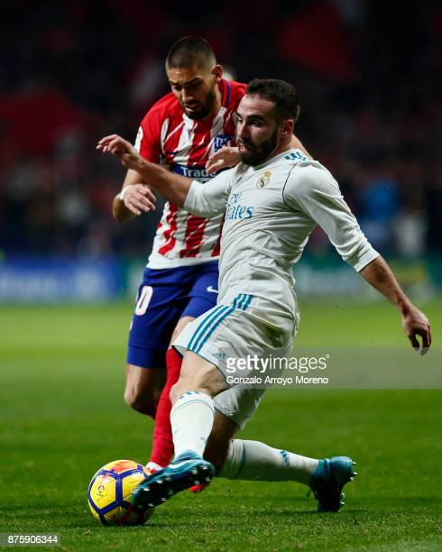 Daniel Carvajal of Real Madrid CF competes for the ball with Yannick Carrasco of Atletico de Madrid during the La Liga match between Club Atletico...