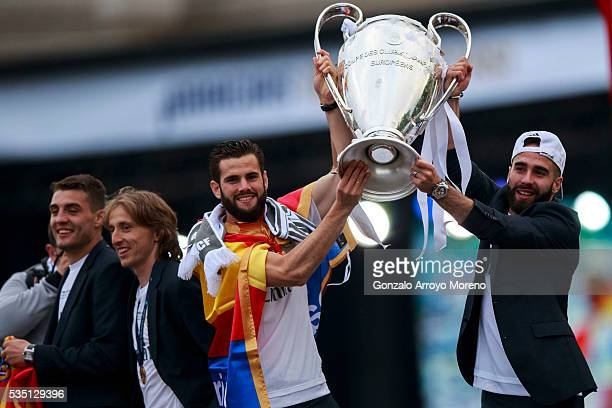 Daniel Carvajal of Real Madrid CF holds the trophy in celebration with his teammate Nacho ahead Mateo Kovacic and Luka Modric during their team...
