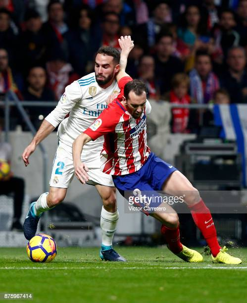 Daniel Carvajal of Real Madrid competes for the ball with Juanfran Torres of Atletico Madrid during the La Liga match between Atletico Madrid and...