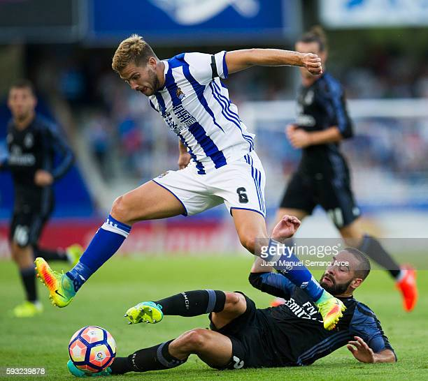 Daniel Carvajal of Real Madrid duels for the ball with Inigo Martinez of Real Sociedad during the La Liga match between Real Sociedad de Futbol and...