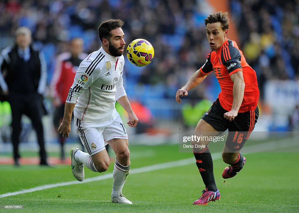 Daniel Carvajal of Real Madrid is tackled by Sergio Canales of Real Sociedad Club De Futbol during the La Liga match between Real Madrid CF and Real Sociedad de Futbol at Estadio Santiago Bernabeu on January 31, 2015 in Madrid, Spain.
