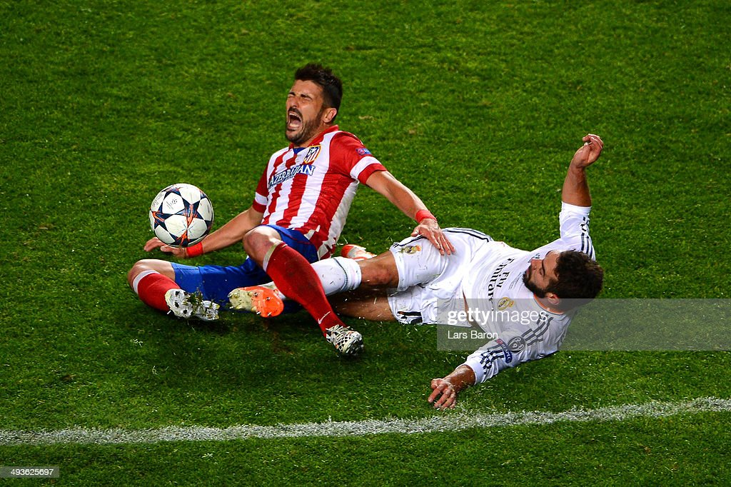 Daniel Carvajal of Real Madrid slides in to tackle <a gi-track='captionPersonalityLinkClicked' href=/galleries/search?phrase=David+Villa&family=editorial&specificpeople=467566 ng-click='$event.stopPropagation()'>David Villa</a> of Club Atletico de Madrid during the UEFA Champions League Final between Real Madrid and Atletico de Madrid at Estadio da Luz on May 24, 2014 in Lisbon, Portugal.